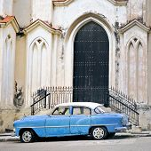 A view of classic american old car parked in front of Havana building facade