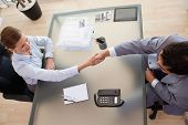 Above view of young consultant shaking hands with customer