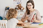 A Young Child Development Therapist  Working With A Child To Overcome His Problems poster
