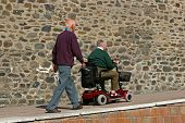 Disabled elderly man riding a mobility vehicle on an uphill path, with another elderly man walking b