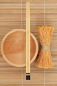 Japanese beech wood bowl with chopsticks and whisk on bamboo mat.