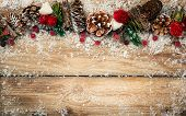 Winter background with rustic Christmas garland.Using pine cones,dried leaves and berries, twigs and poster