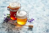 Jars with different kinds of fresh organic honey placed in a row on a blue stone background poster