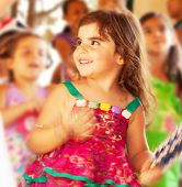 Happy smiling baby girl, adorable cheerful female child enjoying dance on carnival festival, sweet k