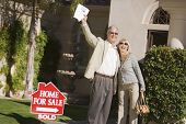 Excited couple standing in front of house with a For Sale Sold sign