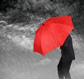 Businessman with red umbrella protecting himself from the storm concept for protection from recessio