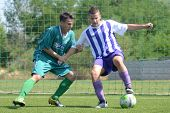 KAPOSVAR, HUNGARY - AUGUST 18: Unidentified soccer players in action at the Hungarian National Championship under 18 game between Kaposvar (green) and Ujpest (purple) August 18, 2012 in Kaposvar.