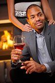 Bem parecido étnico homem sentado por cigarro de fumo de chaminé, beber vinho, namorada de pé atrás