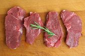 Boneless lamb leg steaks on wooden chopping board.