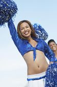 Low angle view of African American woman cheering with pompom and friend in the background