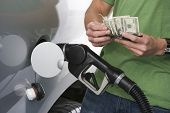 Mid section of a young man counting money while refueling car