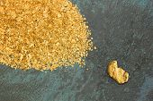 image of gold panning  - Natural placer gold and nuggets in an old gold pan