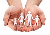Cardboard figures of the family on a white background. The symbol of unity and happiness. Hands gent