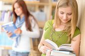 Happy female blonde student at library read books high school