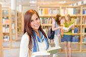 Female teenager student standing and reading book at high-school library