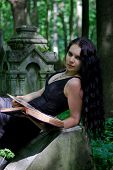 foto of girl reading book  - Gothic girl with old book posing on gravestone - JPG