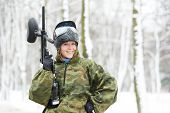 happy female paintball extreme sport player wearing protective mask and comouflage clothing with mar