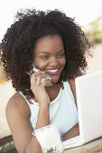 Happy young African American woman with laptop using cell phone