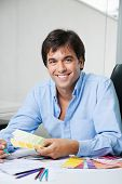 Portrait of young male interior designer smiling while holding color swatches