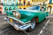 HAVANA-AUGUST 14:Vintage Cadillac in a colorful neighborhood August 14,2012 in Havana.These old cars,the only ones that could be bought until last year,are an iconic sight on the streets of the city