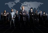 stock photo of crew cut  - business team formed of young businessmen standing over a dark background - JPG