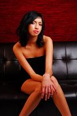 picture of pouty lips  - Attractive young latino woman wearing a sexy dress while sitting on couch - JPG