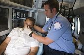 Male EMT professional helping man with oxygen mask inside ambulance