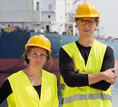 Two Engineering students posing in front of a huge freight vessel during their technological internship in a harbor