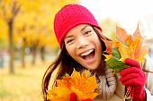 Excited happy fall woman smiling joyful and blissful holding autumn leaves outside in colorful fall
