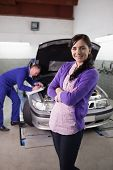 Woman smiling with arms crossed next to a car in a garage