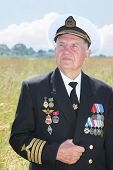 Grandfather in form, cap, ordens, medals hold hand form in field near village