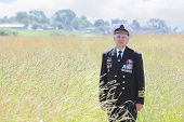 Grandfather in form, cap, ordens, medals pose in field near village