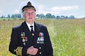 Grandfather in form, cap, ordens, medals pose in field near forest