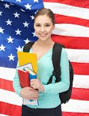 smiling student with books and schoolbag over american flag