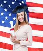 happy student in graduation cap with certificate over american flag