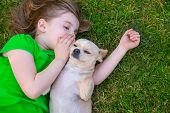 stock photo of baby dog  - Blond happy girl with her chihuahua doggy portrait lying on lawn - JPG