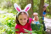 Easter girl with eggs basket and funny bunny face expression at the forest