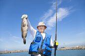 stock photo of grouper  - happy senior fisherman showing large grouper fish - JPG