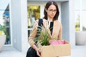 stock photo of unemployed people  - Redundant Businesswoman Leaving Office With Box - JPG