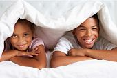 Two Children Hiding Under Duvet In Bed