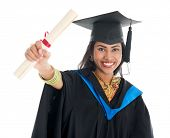 Happy Indian graduate student in graduation gown and cap showing her diploma certificate. Portrait of beautiful Asian female model standing isolated on white background.