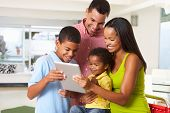 stock photo of 11 year old  - Family Using Digital Tablet In Kitchen Together - JPG
