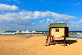 Wooden lifeguard station on empty beach under blue sky with white clouds on Mediterranean sea in Israel.