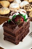 foto of chocolate fudge  - Italian cookies and a decadent slice of chocolate cake with iced flowers and chocolate covered strawberries on a plate with a fork - JPG