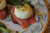 picture of benediction  - This is eggs benedict  up close on a plate on smoked salmon and potato pancake on a plate with asparagus - JPG