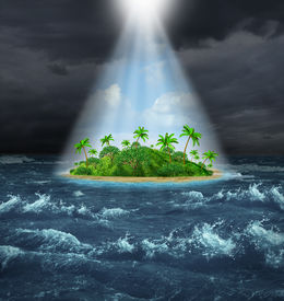 stock photo of oasis  - Hope and aspirations success concept with a dark storm ocean background contrasted with a glowing light from above shinning down on a beautiful tropical island as an oasis vision of the promised land - JPG