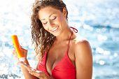 Sunscreen woman. Girl putting sun block on beach holding orange sun tan lotion bottle.