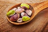 Pistachio nuts in spoon on wooden background