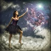 image of reach the stars  - Young woman reaching for a glowing star - JPG