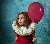 Vintage girl posing with a victorian ruff collar and a red balloon